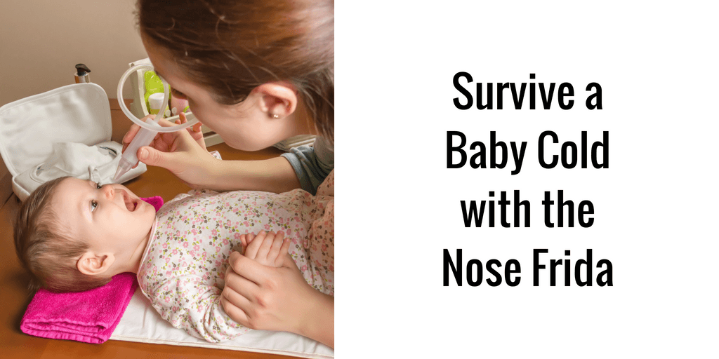 woman using nasal aspirator on baby