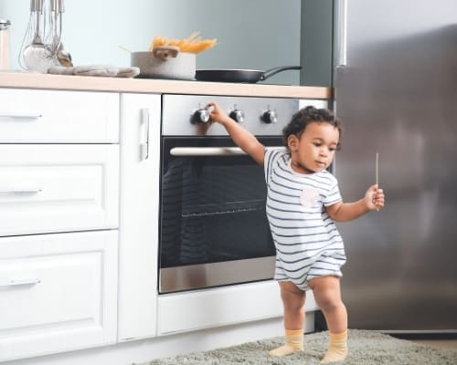 baby touching stove