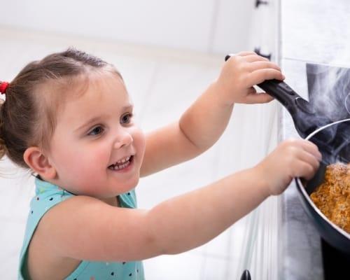 child grabbing hot pan off stove